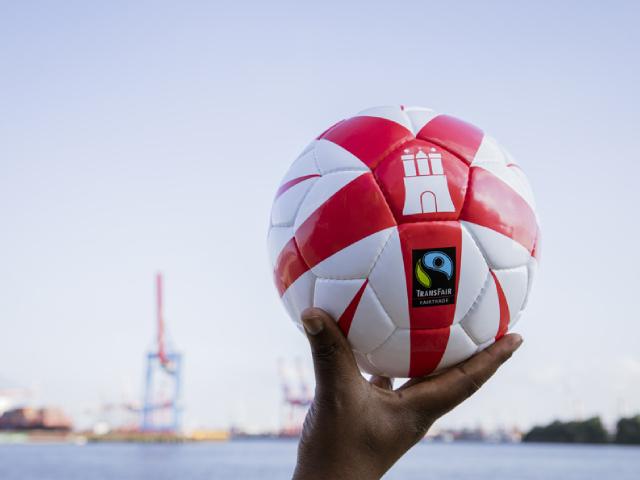 hochgehaltener-fussball-vor-himmel